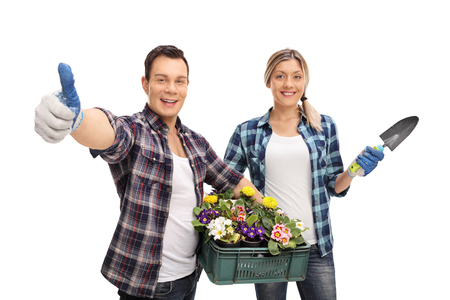 isolated woman: Studio shot of a joyful male and female gardener holding gardening equipment isolated on white background