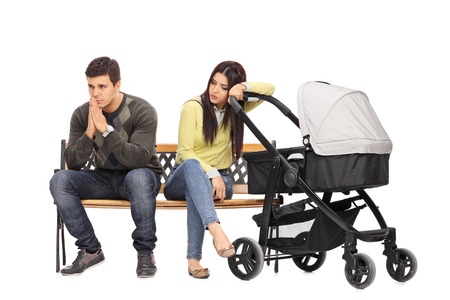 parents with baby: Worried young mother and father sitting on a bench and contemplating isolated on white background