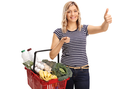 posing  agree: Joyful woman holding a shopping basket and giving a thumb up isolated on white background