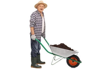 empujando: trabajador agrícola madura empujando una carretilla llena de tierra aislada en el fondo blanco