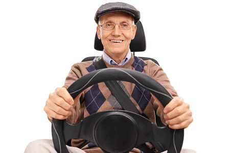 Studio shot of a senior driver holding a steering wheel and looking at the camera isolated on white background