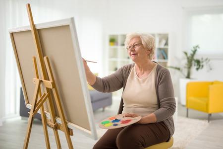 Oudere dame schilderen op een doek met een penseel thuis Stockfoto