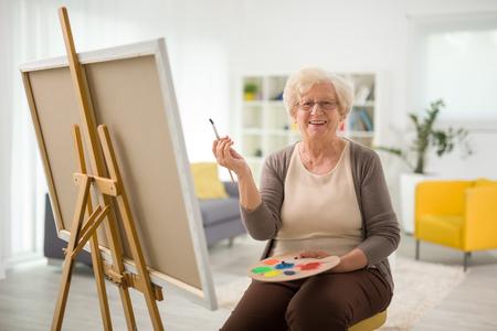 Ältere Frau Malerei auf einer Leinwand auf einem Stuhl zu Hause sitzen