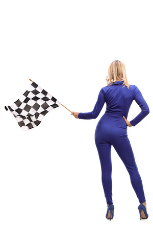 racer flag: Full length rear view studio shot of a racing woman waving a checkered race flag isolated on white background Stock Photo