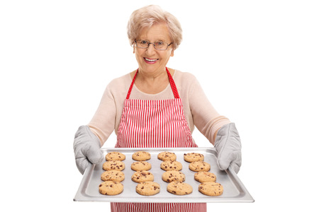 chocolate chip cookies: Mature lady handing a tray full of chocolate chip cookies and smiling isolated on white background Stock Photo