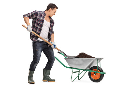 shovel in dirt: Young worker loading dirt into a wheelbarrow with a shovel isolated on white background Stock Photo