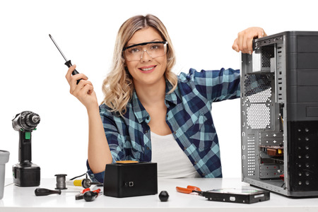 computer isolated: Female PC technician posing next to a disassembled desktop computer isolated on white background Stock Photo