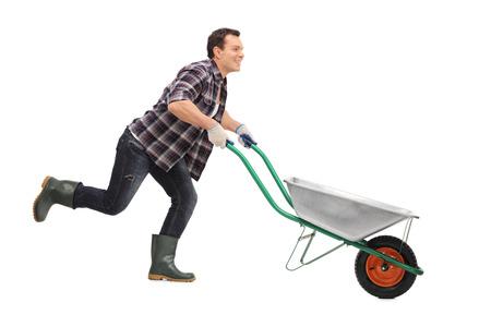 carretilla de mano: jardinero feliz que empuja una carretilla vacía y funcionamiento aislado en el fondo blanco Foto de archivo