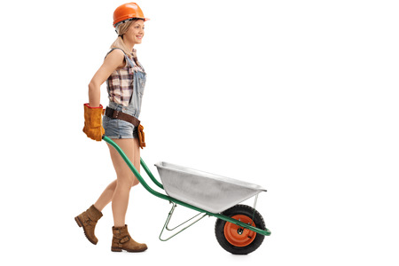 female construction worker: Female construction worker pushing an empty wheelbarrow isolated on white background Stock Photo