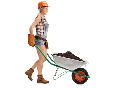 dirt background: Young female construction worker pushing a wheelbarrow full of dirt isolated on white background