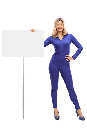 personas mirando: Full length portrait of an attractive young woman standing next to a blank signboard isolated on white background
