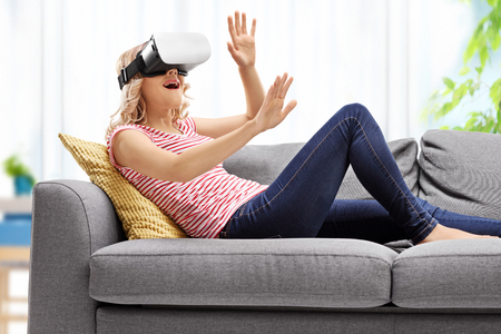 experiencing: Young woman experiencing virtual reality seated on a couch at home Stock Photo