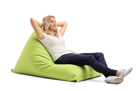 beanbag: Relaxed young woman sitting on a comfortable green beanbag isolated on white background
