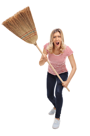 screaming: Vertical shot of an angry woman threatening with a broom and shouting towards the camera isolated on white background