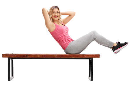 benches: Female athlete doing abdominal crunches on a bench and looking at the camera isolated on white background