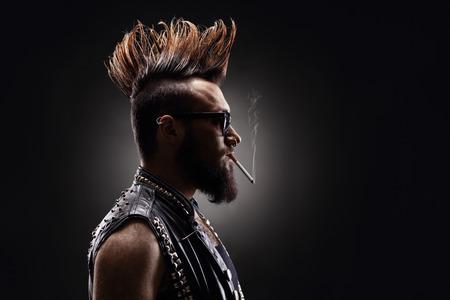 foto de perfil de un rockero punk fumando un cigarrillo sobre un fondo oscuro
