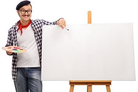 Excentrieke kunstenaar poseren naast een leeg doek op een houten ezel op een witte achtergrond