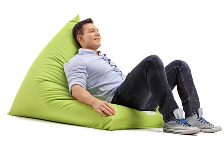 comfortable: Relaxed young guy sitting on a soft and comfortable green beanbag isolated on white background