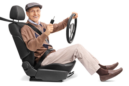vehicle seat: Cheerful senior man holding a steering wheel and a car key seated on a vehicle seat isolated on white background