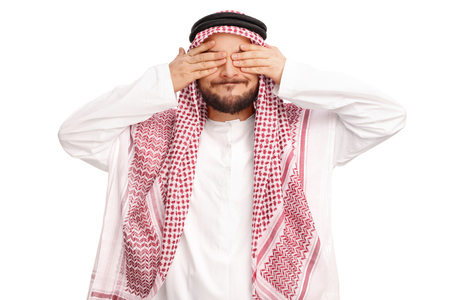 ignorant: Studio shot of a young Arabian man covering his eyes isolated on white background Stock Photo