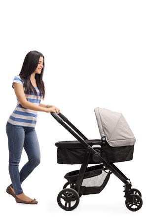 empujando: Retrato de cuerpo entero de una joven madre empujando un cochecito de bebé aislado en el fondo blanco