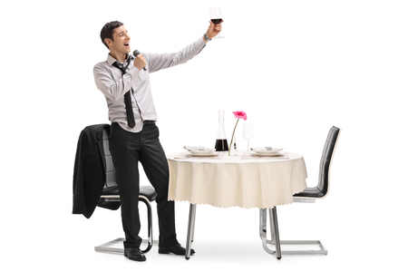 mics: Drunk young man holding a glass of wine in a restaurant and singing on a microphone isolated on white background Stock Photo