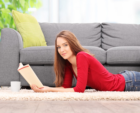 woman laying: Young brunette woman laying on the floor and reading a book at home
