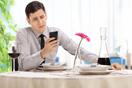 stood up: Disappointed young man sitting at a restaurant table and reading a text message on his cell