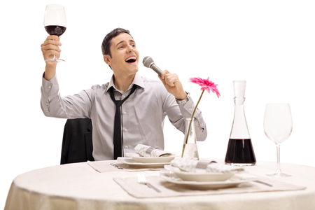 Drunk businessman holding a glass of wine and singing seated at a restaurant table isolated on white background