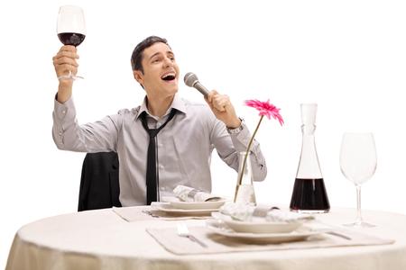tomando vino: negocios borracho que sostiene una copa de vino y el canto sentado en una mesa de restaurante aislado en fondo blanco