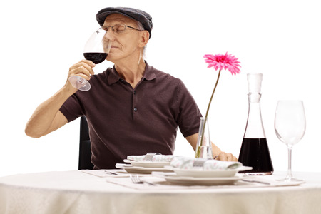 taster: Senior gentleman holding a glass of wine and smelling the wine seated at a restaurant table isolated on white background
