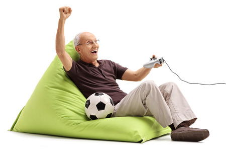isolated on green: Excited senior man playing a soccer videogame seated on a green beanbag isolated on white background Stock Photo