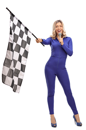white suit: Full length portrait of a racing woman waving a race flag and speaking on a microphone isolated on white background Stock Photo