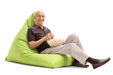 beanbag: Senior man eating popcorn seated on a green beanbag and looking at the camera isolated on white background Stock Photo