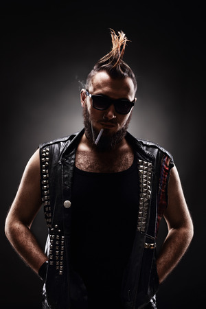 delinquent: Vertical shot of a male punk with Mohawk hairstyle smoking a cigarette on dark background
