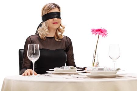 Jonge vrouw met een blinddoek op haar ogen zitten aan een romantisch diner tafel op een witte achtergrond