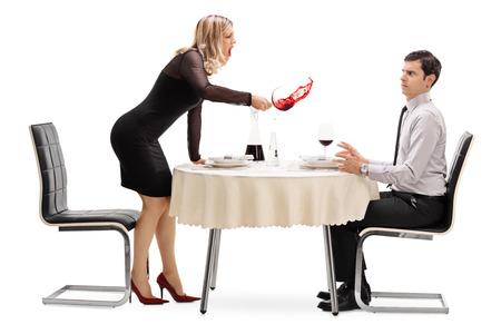 Donna arrabbiata rovesciando il suo drink in un uomo e urlando a lui su un tavolo del ristorante isolato su sfondo bianco