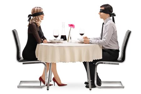 젊은 남자와 여자는 흰색 배경에 고립 된 레스토랑 테이블에 장착 된 블라인드 데이트에 스톡 콘텐츠