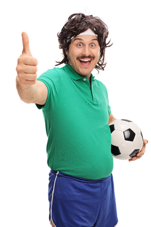 posing  agree: Vertical shot of a retro man holding a football and giving a thumb up isolated on white background Stock Photo
