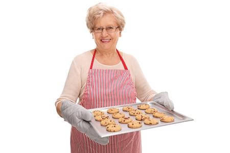 dame d'âge mûr Enthousiaste tenant un plateau plein de biscuits faits maison aux pépites de chocolat isolé sur fond blanc Banque d'images