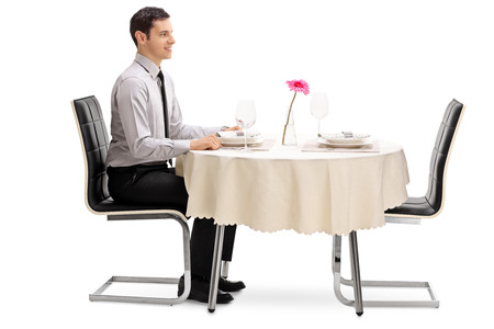 isolated man: Young man sitting at a restaurant table and waiting for his date isolated on white background