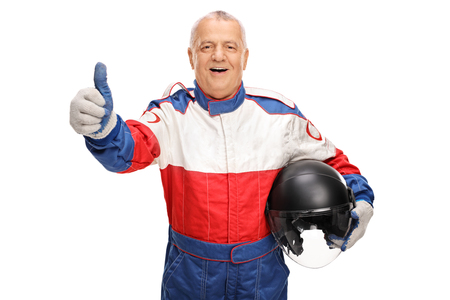 posing  agree: Mature car racer giving a thumb up and holding a helmet isolated on white background