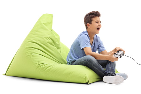 child laughing: Joyful boy playing video games and laughing seated on a green beanbag isolated on white background