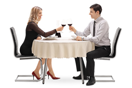 man sit: Young man and woman drinking red wine on a romantic date isolated on white background Stock Photo