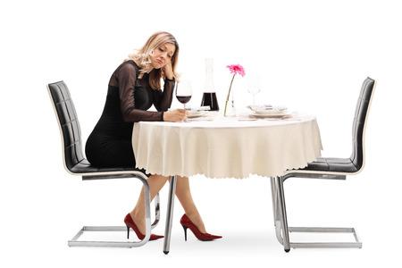 date: Einsame junge Frau, die an einem Tisch im Restaurant sitzen und Wein trinken isoliert auf weißem Hintergrund