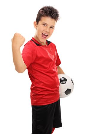 흰색 배경에 고립 된 주먹으로 주먹으로 즐거운 주니어 축구 선수의 세로 샷 스톡 콘텐츠