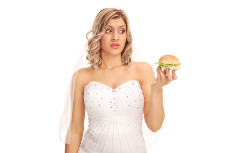 indecisive: Indecisive bride looking at a tempting sandwich isolated on white background