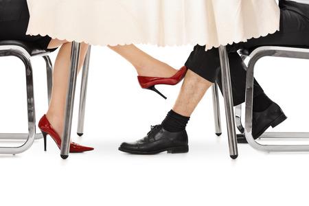 Close-up auf eine Frau, die einen Mann unter einem Tisch mit dem Fuß auf weißem Hintergrund zu berühren
