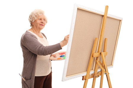 happy senior: Senior female artist painting on a canvas with a paintbrush isolated on white background Stock Photo