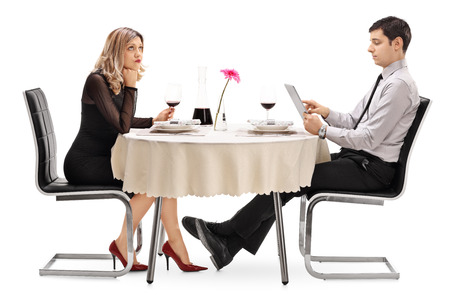 白い背景で隔離のタブレットで遊ぶ男の日付の上に座って退屈女性
